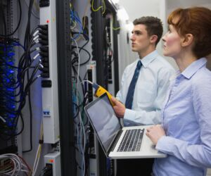 serwer Team of technicians using digital cable analyser on servers in large data center